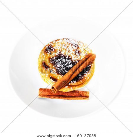 Traditional portuguese pastry - Pastel de nata with curstard cream and sugar powder on a white plate isolated on white macro