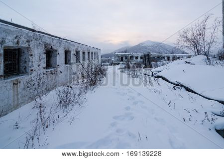 Abandoned prison settlement with decayed buildings in Kolyma winter view