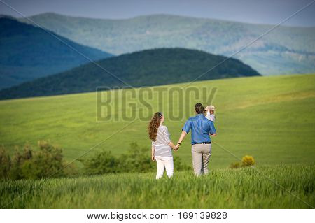 Beautiful young family with little son on a walk against green fields and hills. Rear view.