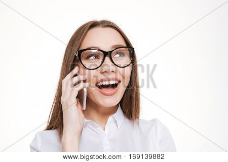 Close up portrait of happy beautiful business woman in glasses talking on mobile phone over white background