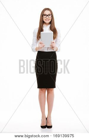 Full length portrait if a smiling happpy businesswoman holding tablet computer isolated on a white background
