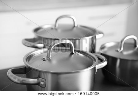 Kitchenware concept. Stainless saucepans on grey kitchen table, closeup