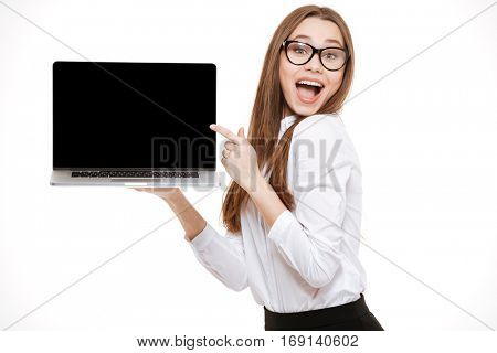 Happy excited business woman holding laptop and pointing on it isolated on a white background