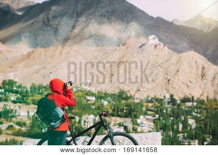 young woman taking photograph with her bicycle in the himalaya range.
