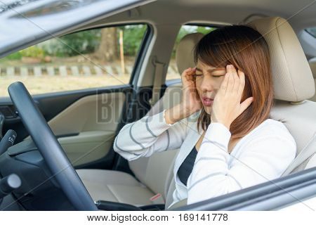 Closeup portrait of young woman touching her temple feels headache in her car after driving car for long time.