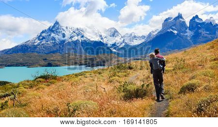 family of two father and son enjoying hiking and active travel in torres del paine national park in patagonia chile view of cuernos del paine and pehoe lake