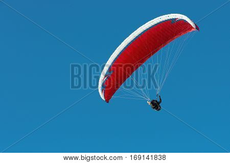 Paraglider flying in a beautiful blue sky