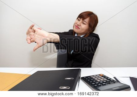 Businesswoman stretching herself or exercise while working at office - office syndrome concept