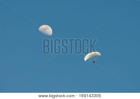 Paragliding with the moon in the blue sky at daylight