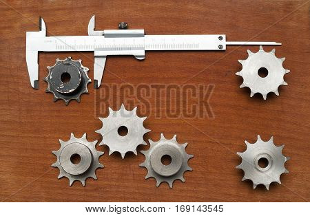 Engineering tools gears and caliper on wooden table. Success concept. Top view Copy space for text.