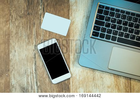 Laptop computer smart phone and business card on rustic wooden office desk top view mock up copy space