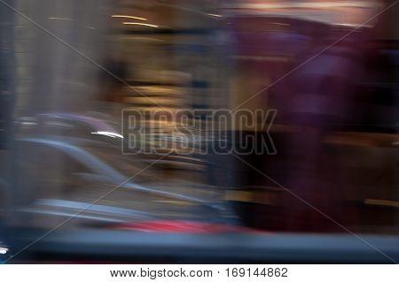 Defocused store window with cars and pedestrians motion blur vintage retro shot