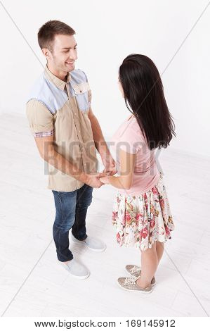 Young couple in love holding hands. Unusually top view on white
