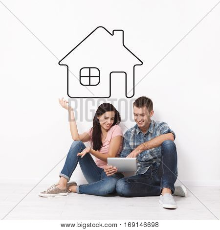 Happy young couple sitting on the floor using a tablet for shopping and entertainment. Layout. Drawing house as a background.