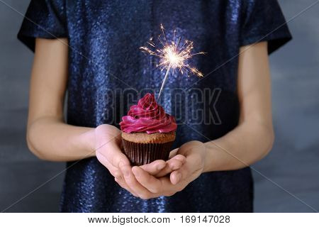Woman holding tasty cupcake with sparkler, close up