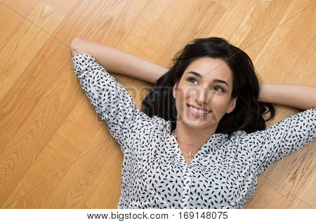 Happy young woman lying on wooden floor relaxed at home looking up. Top view of girl lying on wooden floor smiling and thinking. High angle view of smiling woman relaxing on floor and daydreaming.