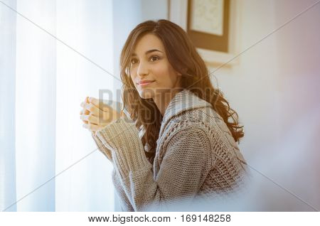 Woman drinking hot tea. Happy young woman enjoying hot drink on a bright morning at home with warm sweater. Pensive girl sitting in front of the window while drinking hot coffee in a winter afternoon.