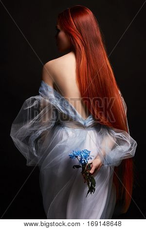 Sexy beautiful redhead girl with long hair in dress cotton retro. Woman portrait on black background. Deep eyes. Natural beauty clean skin facial care and hair. Strong and thick hair. Flower