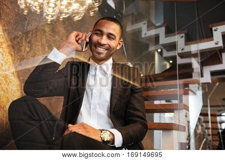 View from below of smiling african man in suit talking at phone and sitting on stairs in hotel