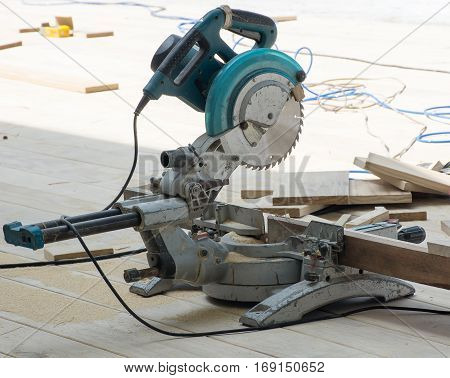 Circular saw or carpenter tools put on the wooden floor in sunny day.