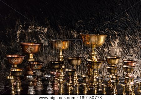 A lot of cups fill fuel got light for praying to god in tibetan buddhism on texture of wall background.