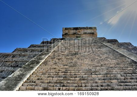 Steep steps leading up chichen itza temple in bright sun