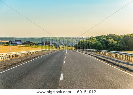 Slope rural asphalt road with marking and guard rails. Belgorod region Russia.