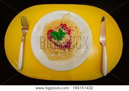 Penne pasta in tomato sauce with chicken, tomatoes decorated with parsley on a wooden table. Pasta dish with knife and fork