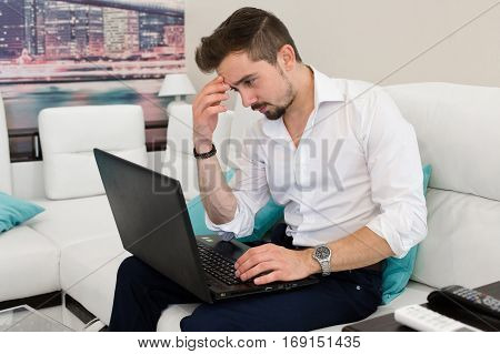Thinking handsome man working t laptop at home. Young man relaxing on the sofa with a laptop. Multitasking.Handsome young man wearing glasses and working with touchpad while sitting on couch in office