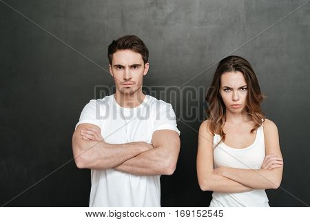 Offended young couple standing with crossed arms in studio. Isolated dark background