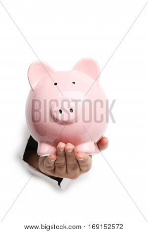 Male hand with piggybank punching through the paper