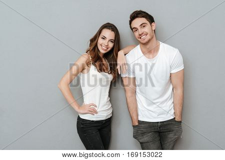 Young Happy Couple posing in studio. Man standing with arms in pockets. Isolated gray background