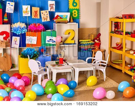 Kindergarten interior decoration child picture on wall. Preschool class waiting kids. Colour balloons on floor. Playroom with white table. Art room for education children's creativity.