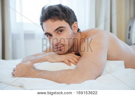 Naked calm man lying on bed and looking at camera. Side view
