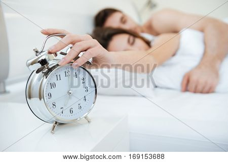 Couple sleeping on bed. Focus on clock. Girl turns off the alarm
