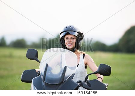 Pretty blond woman enjoying a motorbike ride outdoors in green nature.