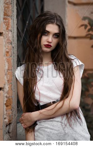 Beautiful goth girl.black flower in hand of young woman.halloween concept.gothic make-up.Horror woman. Scary Girl and Halloween theme: portrait of a crazy girl with a bloody face in the studio