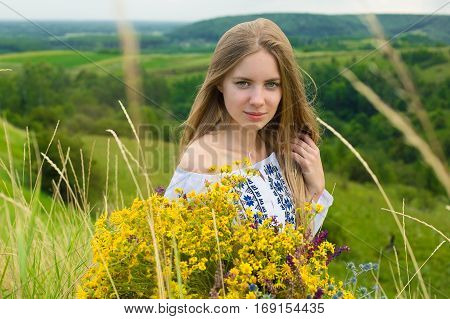 Outdoor portrait of beautiful blonde woman, attractive young girl in camomile field with flowers. Young beautiful girl in the field in summertime. Cosmos flowers in hands. Girl with bouquet of flowers