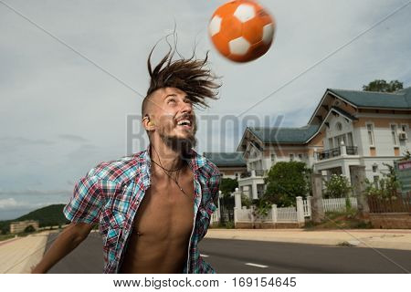Atractive man spinning a ball on his finger on the street