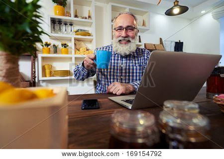 Side low angle of pleased man. Holding a cup of tea. Fashionable mature man working in laptop. Portrait of old man sitting at the wooden table