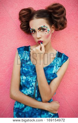 Fashionable image of fashionable model with two hair bun and creative professional makeup posing on pink background. Creative makeup and hairstyle.