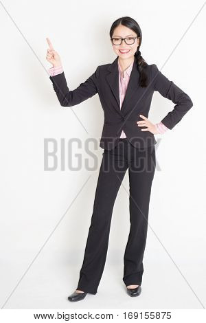 Full body portrait of young Asian businesswoman in formalwear fingers pointing at copy space and smiling, standing on plain background.