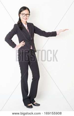 Full length front view of young Asian businesswoman in formalwear hand displaying something, standing on plain background.