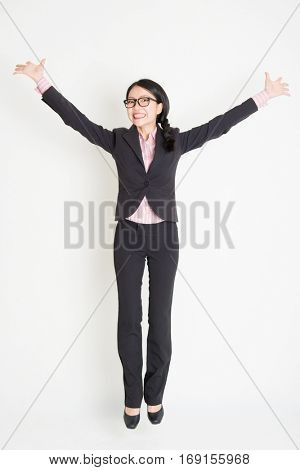 Full length front view of young Asian businesswoman in formalwear jumping in midair, on plain background.
