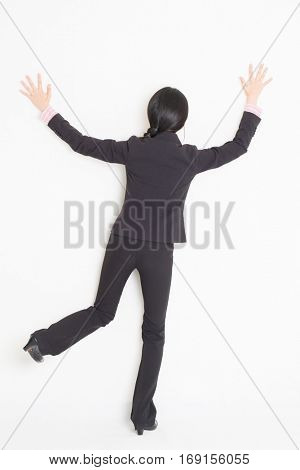 Full body back view of young Asian businesswoman in formalwear banging and leaning on wall, standing on plain background.
