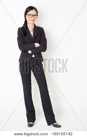 Full body portrait of young Asian businesswoman in formalwear arms folded and smiling, standing on plain background.