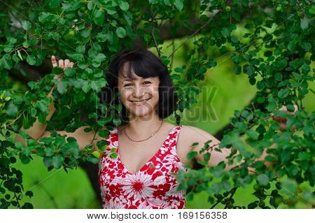 The happiest woman in the world with amazing beautiful white smile standing in green trees in summertime. Beautiful attractive pretty woman with white smile standing on greenery background outdoors.