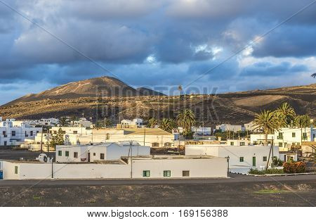 View On Traditional Whitewashed Village With Volcanos On The Background In The Evening On Lanzarote