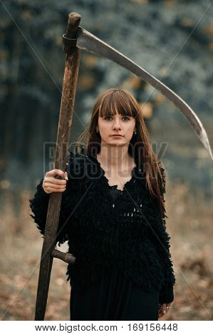 Beautiful mysterious mystical girl with long hair in black dress holding a braid in dark autumn forest on the way. Mystical pretty girl in all black clothes with braid stand in dark mystical forest