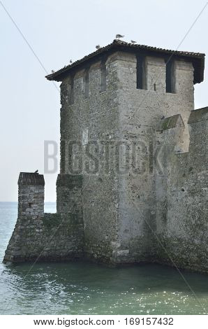 SIRMIONE, ITALY - AUGUST 7, 2014: Tower of medieval port fortification at Sirmione on lake Garda Italy.